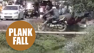Motorbiker tries to drive across a plank footbridge only meant for people