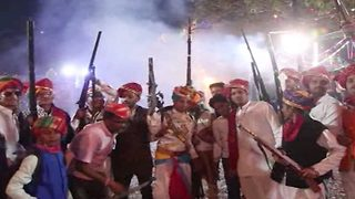 Bizarre ritual: Frenzied locals fire bullets in air to celebrate festival of 'colours' - Video
