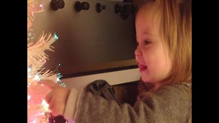 Little Girl is Amazed by her Glowing Christmas Tree