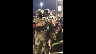 Woman arrives from army posting overseas to surprise little sister at graduation - Video