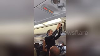 Air hostess struggles through safety routine as football fans make her laugh - Video