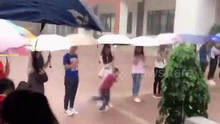 Chinese teachers hold umbrellas for schoolchildren during downpour - Video