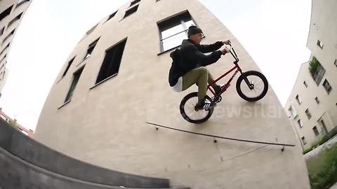 BMX biker rides down walls, over bins and benches