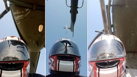 Thrill seeking motorcyclist rides under helicopter flying just nine feet off the ground