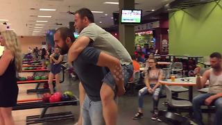 Man scores strike while piggyback riding - Video