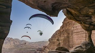 Up, up and away! Incredible images of paramotorist gliding above ruins of Jordan