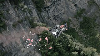 Wingsuit pilot becomes first to fly through moving target - Video