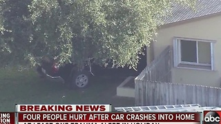 Four people hurt after truck crashes into home - Video