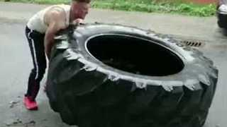 Impressively Strong Man Continuously Flips Giant Tire Along Road - Video
