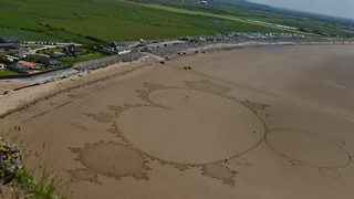 Sand artist uses entire beach to create incredible drawing - Video