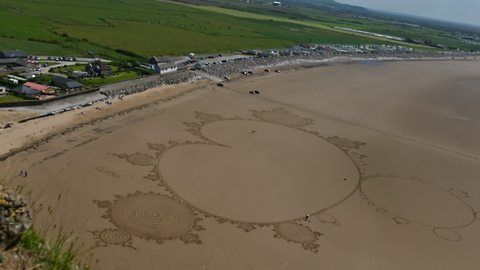 Sand artist uses entire beach to create incredible drawing
