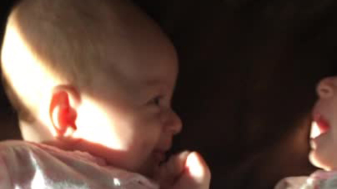 Newborn twin girl amused by crying sister