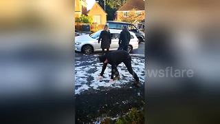 Man struggles to stand up on icy pavement