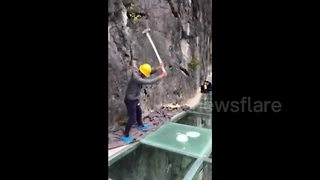 Men hit dizzyingly high glass walkway with sledgehammers - Video