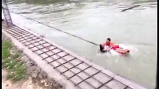 Firefighters rescue woman from being swept away by rapid water in southern China