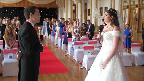 Bride And Groom Sing Duet Down Wedding Aisle