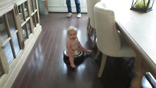 """""""A Baby Boy Rides on A Roomba Vacuum Cleaner"""""""