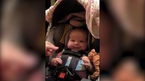 A Baby Boy Makes Funny Faces When His Mom Tightens Up His Baby Seat