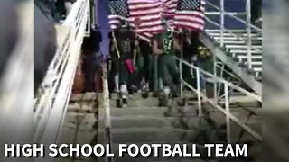 High School Football Team Enters Stadium Carrying American Flags - Video