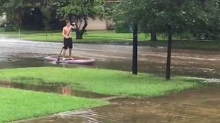 Man Paddle Boards Through Flooded Houston Neighborhood - Video