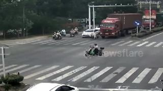 Scooter rider narrowly escapes being run over by lorry - Video
