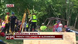 Officials work to save man from collapsed trench - Video