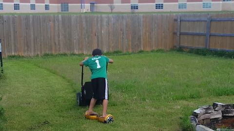A Boy Rides A Hoverboard While He Mows The Lawn With A Push Mower