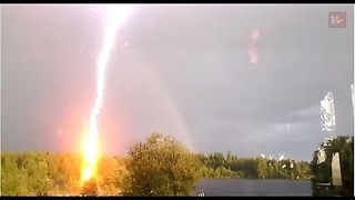 Powerful lightning strike after the rainbow, Blaiken Storuman, Sweden.
