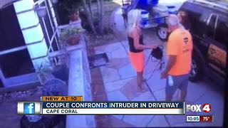 Surveillance video shows couple confronting intruder breaking into their car - Video