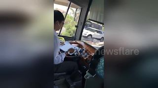 Vietnam bus driver uses TWO hands to make notes while driving on highway - Video
