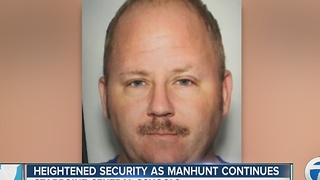 Heightened security as search for man continues - Video