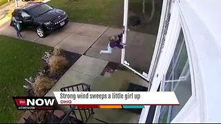 Surveillance video captures girl being blown away by high winds - Video