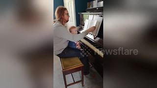 Baby waits for page to turn before playing piano - Video