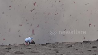 Volcano erupts as man stands next to crater - Video