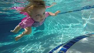 Swimming babies float and dive for rings