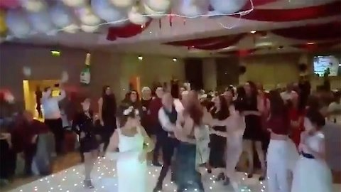 Playful scuffle breaks out at wedding celebrations as guest tackles maid of honour for bouquet
