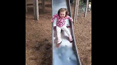 Little girl totally wipes out going down slide