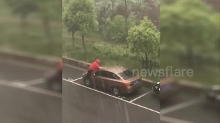 Chinese man washes car in torrential rain - Video
