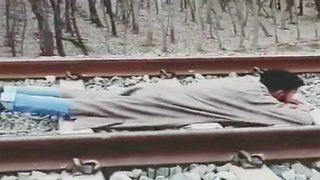 Death-defying stunt: Young Kashmir man lies on railway track as speedy train passes over him - Video