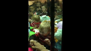 A Tot Boy Sits Inside Of A Claw Machine Game And Plays With Toys