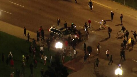 Man detained after hitting protesters with his car, police say