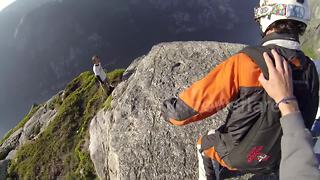 Sheer madness! Daredevils perform headfirst base jump down cliff face - Video
