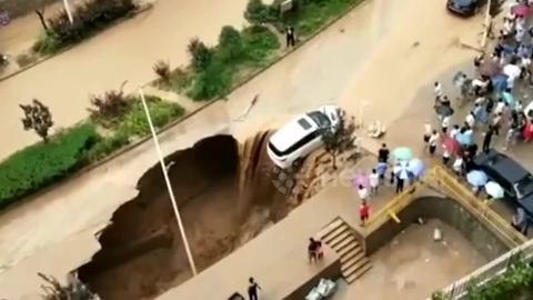 Good Samaritans team up to pull a car away from a huge sinkhole