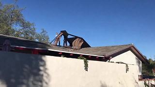 Strong winds carry gazebo onto roof - Video