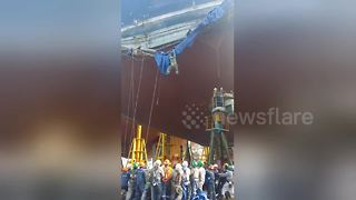 Workers filmed clinging on for life after cargo ship scaffolding collapses - Video