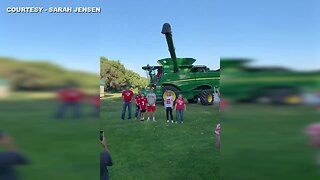 Daughter surprises parents with gender reveal using combine