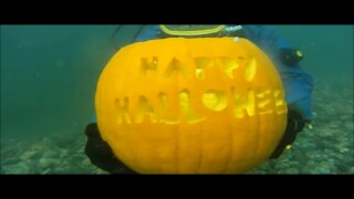 Scuba divers perform underwater pumpkin carving contest