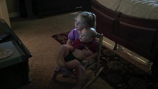 Little Girl Preciously Holds Baby Brother To Watch TV - Video