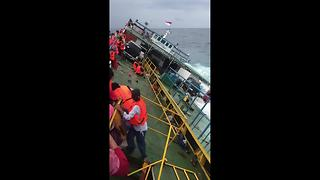 Indonesia ferry tragedy footage shows passengers clinging to side of vessel - Video