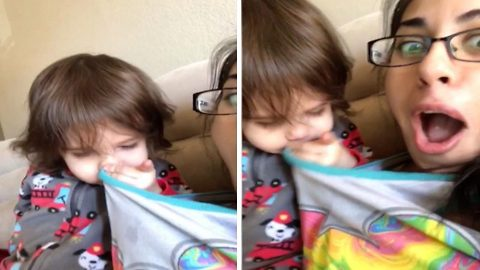 Adorable toddler sneezes and wipes his nose on his mum